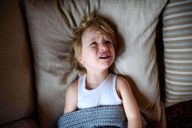 Nachtschreck Pavor Nocturnus bei Kindern. Kind liegt im Bett und schreit hysterisch. Was sind die Ursachen und wie können Eltern bei der Schlafstörung helfen?