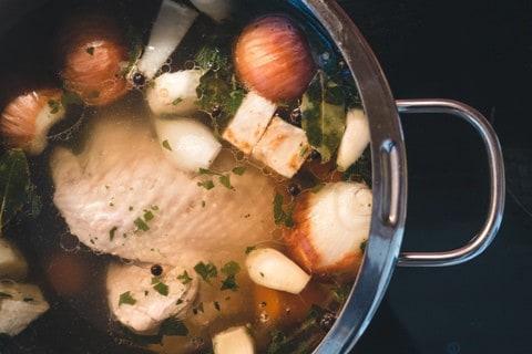 Hühnersuppe zubereiten: Suppenhuhn im Topf - köchelt langsam