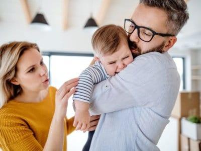 """Vater hält weinendes Baby. Mutter tröstet. Fremdeln auch""""Acht-Monats-Angst"""" genannt. Entwicklungsphase Fremdeln."""