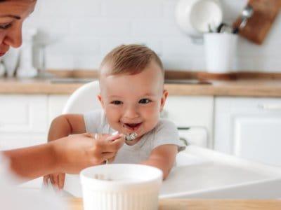 Mutter füttert Baby. Beikostreifezeichen erkennen. Wann ist die richtige Zeit für den ersten Brei.