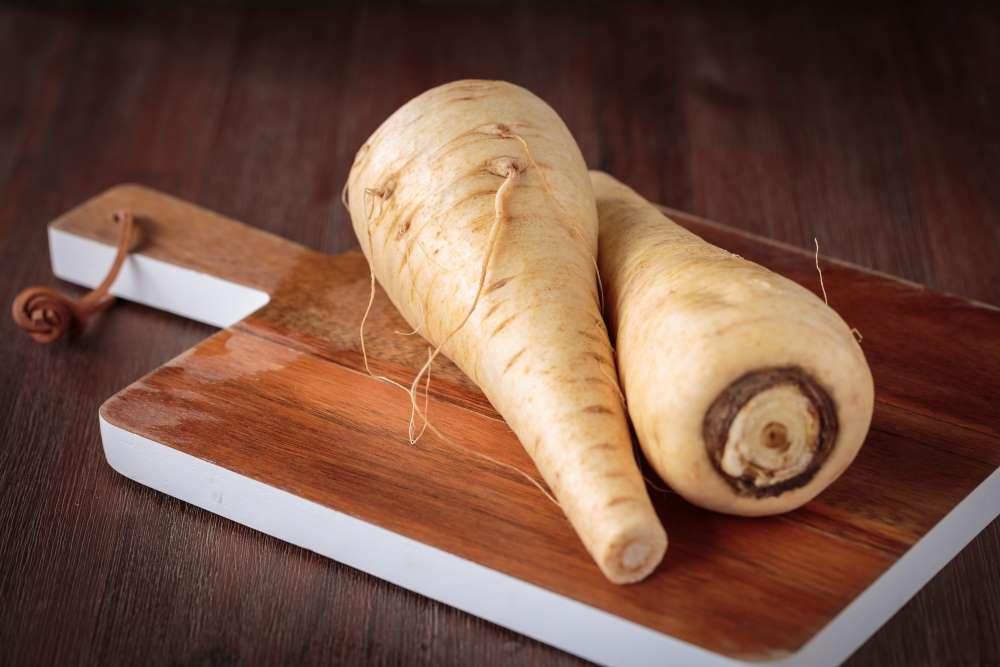 Pastinaken auf Holzbrett. Zubereitung Pastinakenbrei für Baby Beikost. Die Pastinake ist nben Karotten ein beliebtes Gemüse für den Babybrei .
