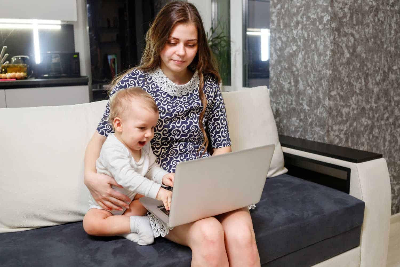 Homeoffice mit Kind: Utopie oder doch möglich? Mutter arbeitet am Laptop - Baby sitzt dabei