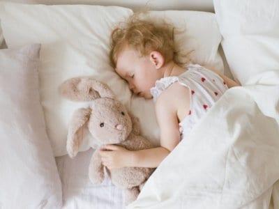 Der Mittagsschlaf: Kleine Erholungspause für das Kind. Kleinkind liegt im Bett und hält ein Mittagsschläfchen.