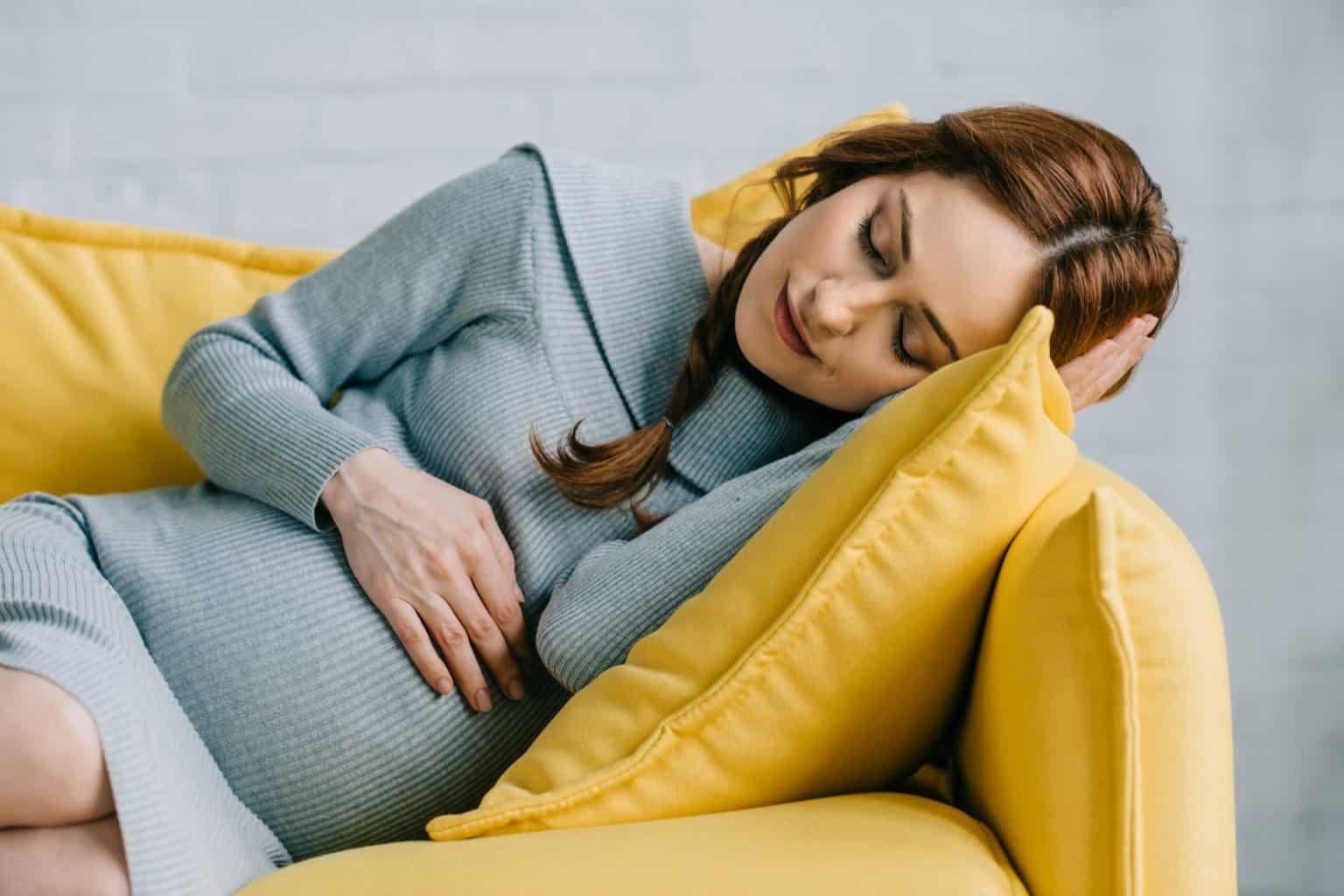 Müdigkeit in der Schwangerschaft. Was tun bei Schwangerschaftsmüdigkeit. Schwangere liegt müde auf dem Sofa.
